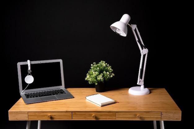 Escritorio de madera con laptop y lámpara.