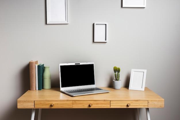 Escritorio de madera con laptop y marcos.