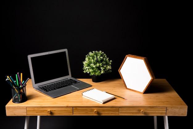 Escritorio de madera con laptop y notebook.