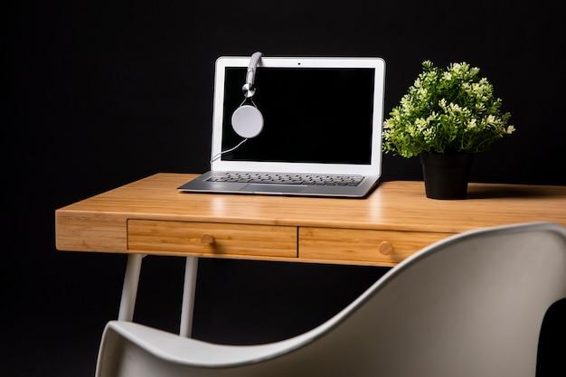 Escritorio de madera con laptop y silla.