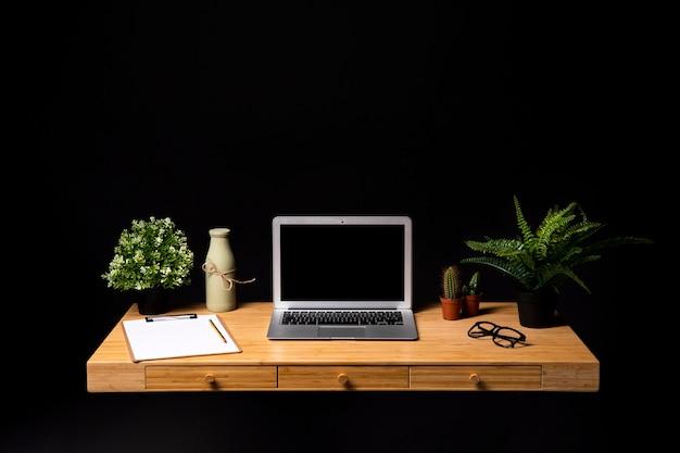 Escritorio de madera ordenada con laptop gris