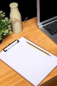 Escritorio de madera con portapapeles y laptop.