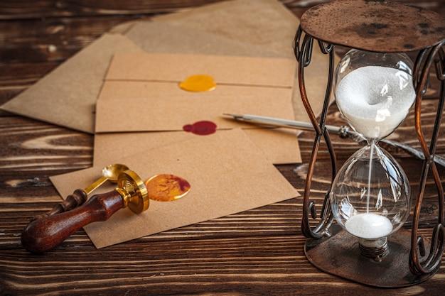 Escritorio de madera con reloj de arena vintage y carta antigua
