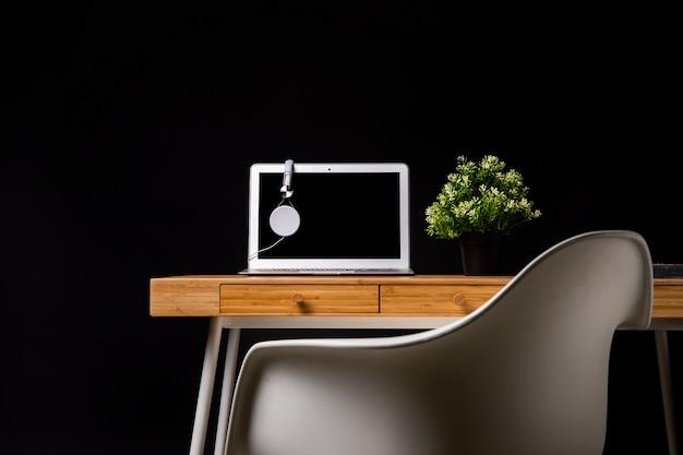 Escritorio de madera con silla y laptop.