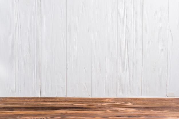Un escritorio de madera vacío contra la pared pintada de blanco.