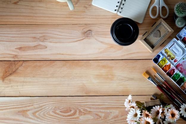 Escritorio de madera de la vista superior de un artista con una gran cantidad de objetos de escritorio.