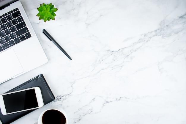 Escritorio de mármol con laptop, café y accesorios.