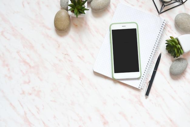 Escritorio de mármol plano de oficina con teléfono, piedras y suculentas.