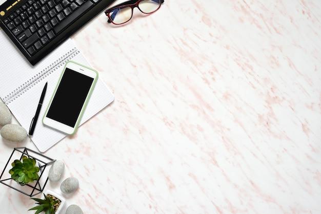 Escritorio de mármol plano de oficina con teléfono, teclado y notebook.