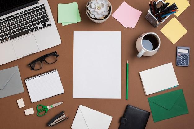 Escritorio marrón con taza de café; portátil y suministros de oficina