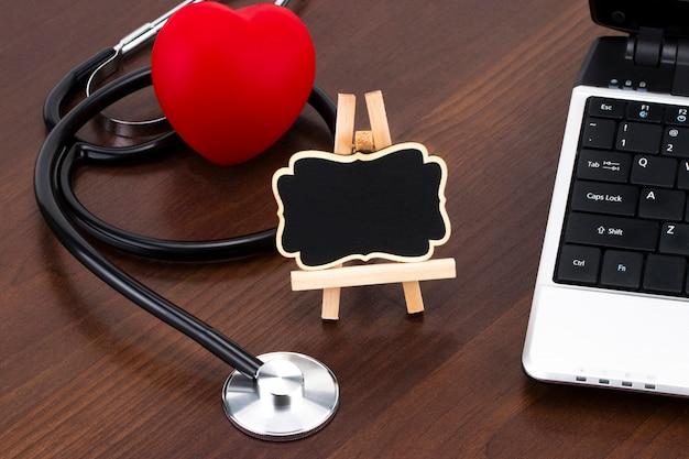 El escritorio del médico con computadora portátil, estetoscopio y corazón rojo y pizarra con espacio vacío para un texto