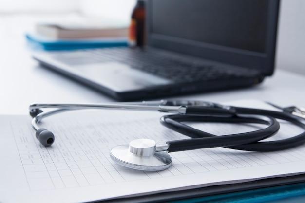 Escritorio del médico con estetoscopio, computadora portátil y documentos