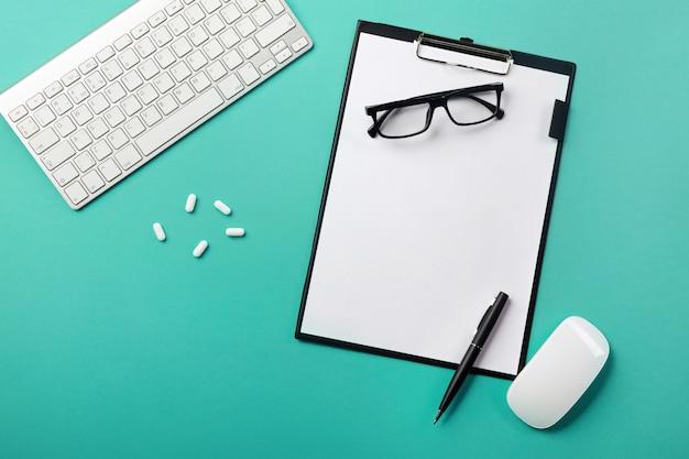 Escritorio del médico con tableta, bolígrafo, teclado, mouse y píldoras.