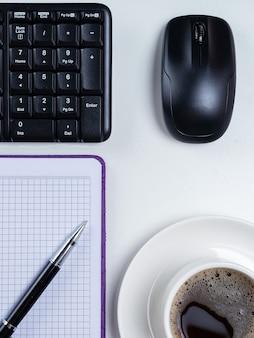 Escritorio de mesa de oficina. espacio de trabajo con cuaderno en blanco, teclado, material de oficina y taza de café sobre fondo blanco.