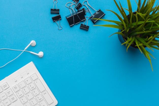 Escritorio de mesa de oficina con suministros en azul, vista superior y espacio de copia para texto