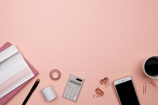 Escritorio de la mesa de oficina con teléfono inteligente y otros suministros de oficina en fondo rosa.