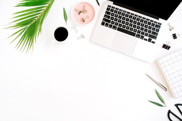 Escritorio de mesa de oficina con vista superior y endecha plana. espacio de trabajo con cuaderno, portátil, rama de palma, taza de café, tijeras y clips sobre fondo blanco.