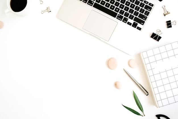 Escritorio de mesa de oficina con vista superior y endecha plana. espacio de trabajo con cuaderno, portátil, taza de café, tijeras y clips sobre fondo blanco.