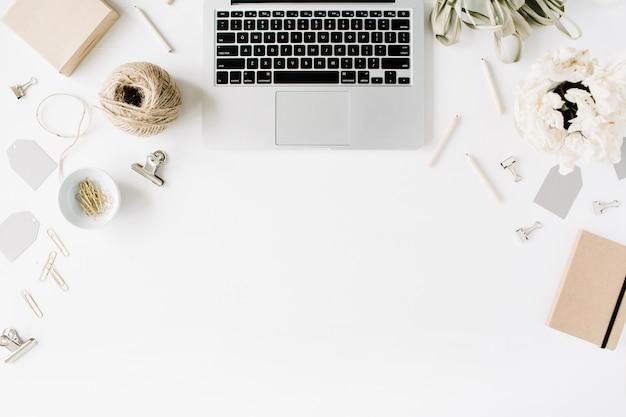 Escritorio de mesa de oficina con vista superior y endecha plana. espacio de trabajo de escritorio femenino con computadora portátil, cordel, lápices, ramo de flores, diario de artesanía y clips sobre fondo blanco.