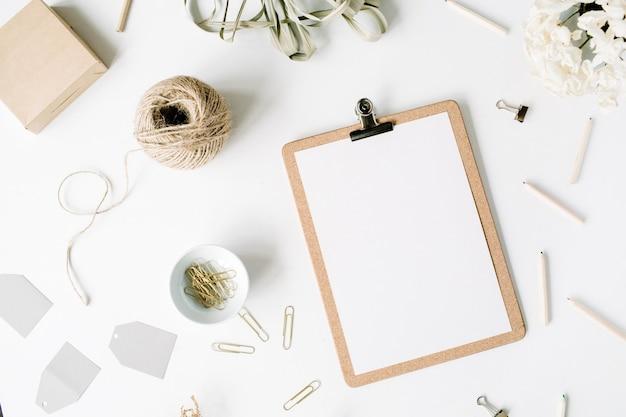 Escritorio de mesa de oficina con vista superior y endecha plana. espacio de trabajo de escritorio femenino con portapapeles, cordeles, lápices, ramo de flores, diario de artesanía y clips sobre fondo blanco.