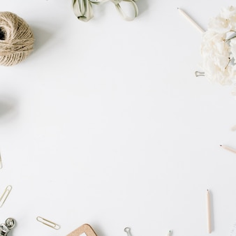 Escritorio de mesa de oficina con vista superior y endecha plana. marco de espacio de trabajo de escritorio femenino con hilo, lápices, ramo de flores, diario de artesanía y clips sobre fondo blanco.
