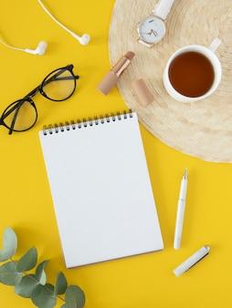 Escritorio de moda minimalista femenino. cuaderno espiral abierto, rama de eucalipto y gafas de sol sobre mesa amarilla. maqueta vertical con espacio para tus deseos.