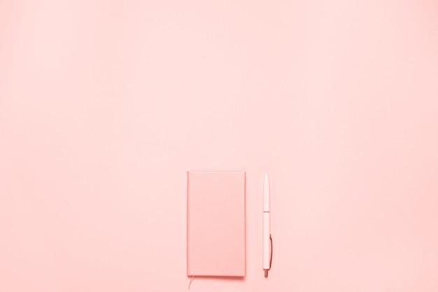 Escritorio moderno de color coral con diario y bolígrafo de color coral. composición minimalista en plano