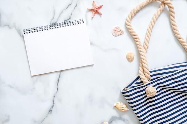 Escritorio de mujer con bolsa de playa a rayas, conchas y bloc de notas en blanco.
