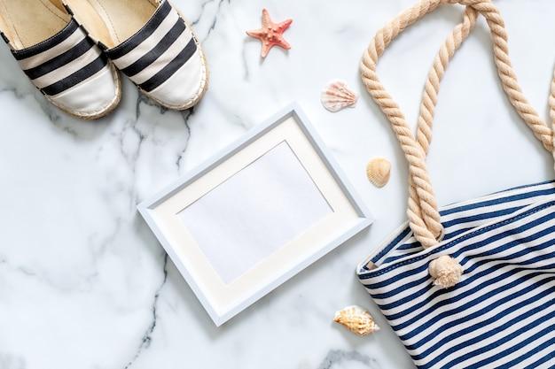 Escritorio para mujer con sandalias de rayas, bolsa de playa, conchas y marco de fotos en blanco.