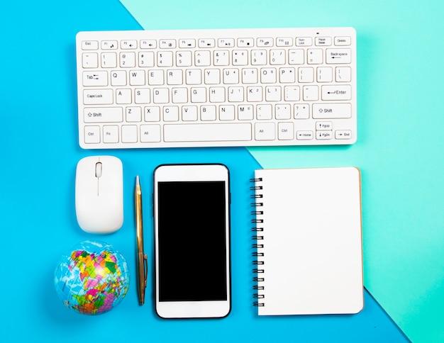 Escritorio de negocios componer con notebook y smartphone en fondo pastel
