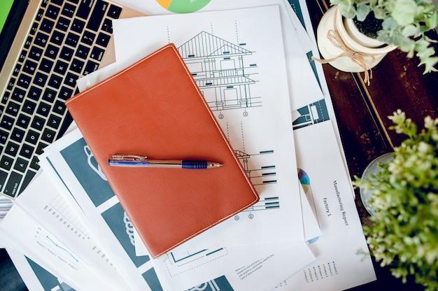 Escritorio de negocios con cuaderno de negocios, escritorio, pluma, papel, tabla, gráfico