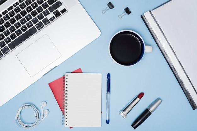 Escritorio de negocios con objetos de maquillaje; taza de café; archivos y auriculares sobre fondo azul