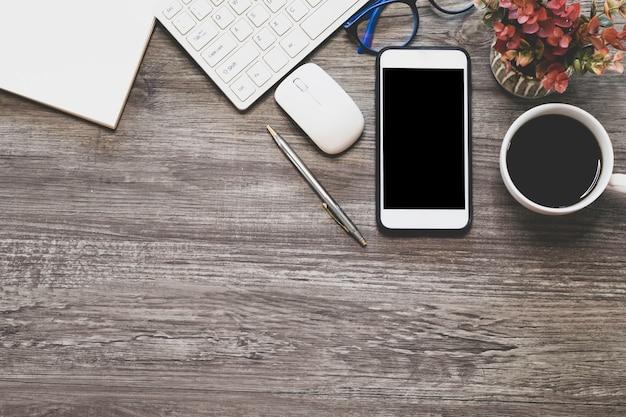 Escritorio de negocios con teléfono inteligente, lápiz, teclado y taza de café en la mesa de madera