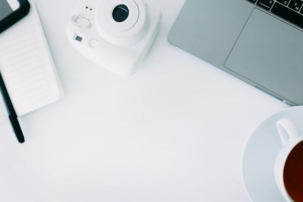 Escritorio de oficina blanco con laptop, cuaderno con bolígrafo, mini cámara y taza de té