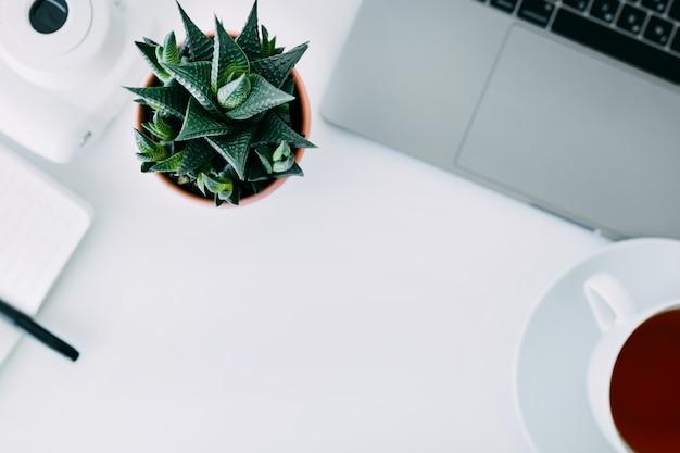 Escritorio de oficina blanco con laptop, planta de oficina y cuaderno con bolígrafo, mini cámara y taza de té. vista superior con espacio de copia, plano.