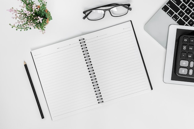 Escritorio de oficina blanco. mesa con cuaderno en blanco, tableta, calculadora, computadora y otros suministros de oficina