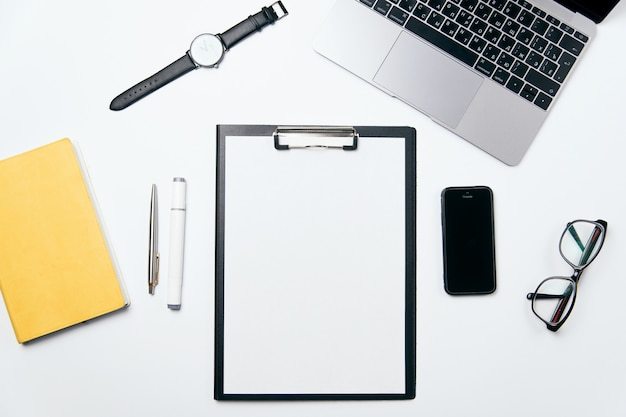 Escritorio de oficina blanco de vista superior con computadora portátil, teléfono, cuaderno, espacio en blanco claro con espacio de copia libre y suministros, fondo plano.