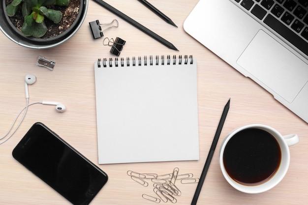 Escritorio de oficina con bloc de notas en blanco, computadora portátil y suministros de oficina