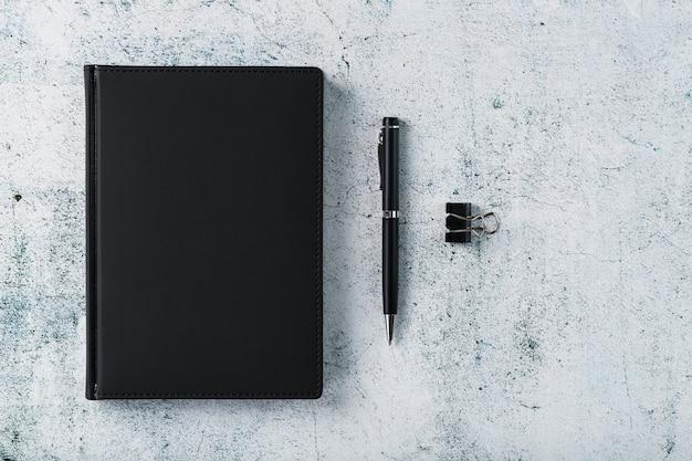 Escritorio de oficina con bloc de notas negro y bolígrafo sobre fondo gris. vista superior con espacio de copia. concepto de metas y objetivos comerciales