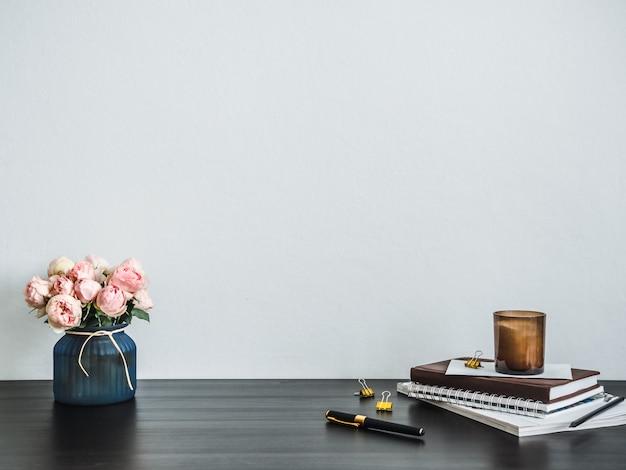 Escritorio de oficina en casa con espacio de copia. flores rosas, velas perfumadas, pila de libros sobre encimera negra.