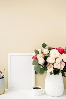 Escritorio de oficina en casa con maqueta de marco de fotos, hermosas rosas y ramo de eucalipto frente a un fondo beige pastel pálido