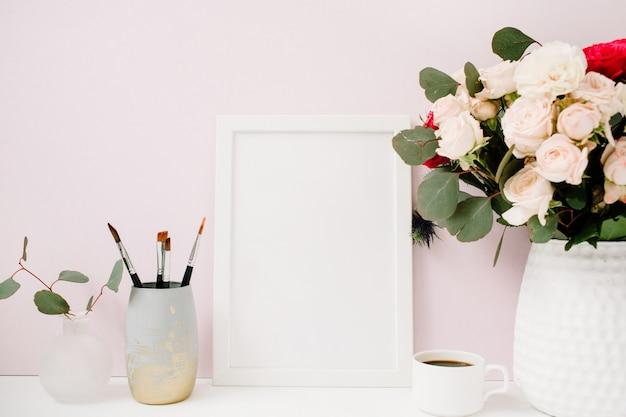 Escritorio de oficina en casa con maqueta de marco de fotos, hermosas rosas y ramo de eucalipto