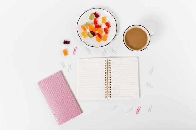 Escritorio de oficina en casa plano. bloc de notas, clips, lápiz, café y dulces