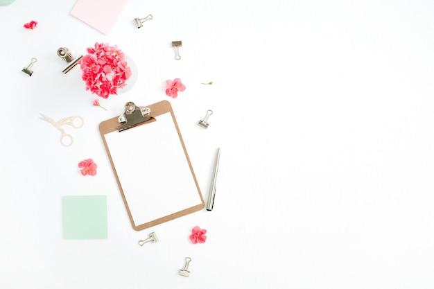 Escritorio de oficina en casa plano. portapapeles con espacio para copiar texto, flores rojas, accesorios, diario de menta en blanco