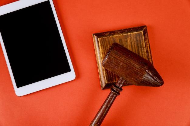 Escritorio de oficina comercial con subasta de mazo de madera y espacio de trabajo de tableta digital en funcionamiento para subasta