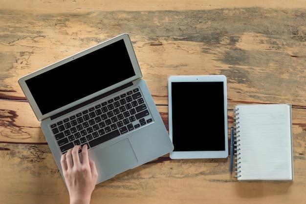 Un escritorio en una oficina con una computadora portátil que está escribiendo un blog. las manos de los hombres en el teclado.