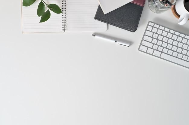 Escritorio de oficina con computadora de teclado, café, papel de cuaderno y material de oficina en el escritorio de la oficina de la vista superior.