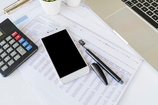 Escritorio de oficina contable con calculadora y teléfono inteligente.