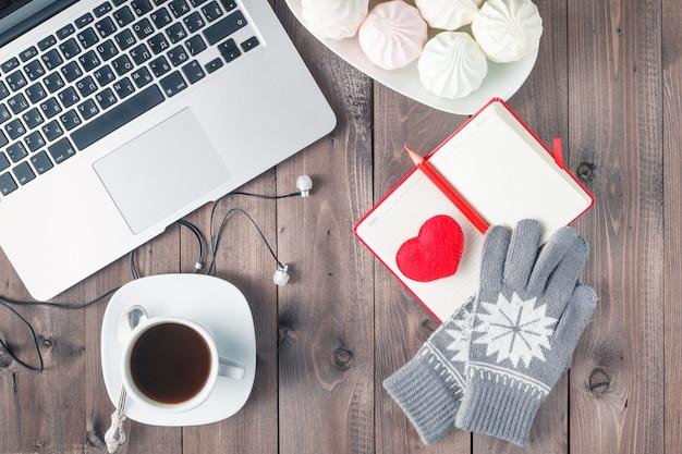 Escritorio de oficina con corazón rojo, cuaderno y dulces. concepto de día de san valentín