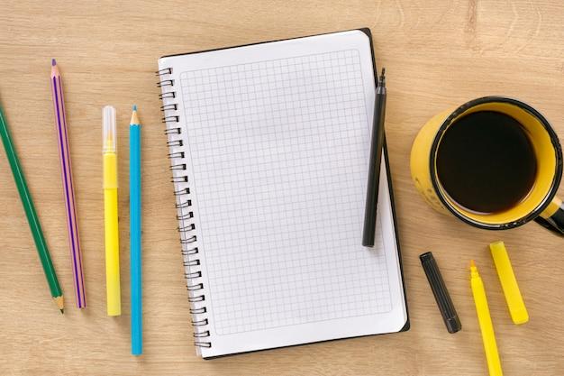 Escritorio de oficina con cuaderno epmty, taza de café, marcadores de colores y vista superior de lápices